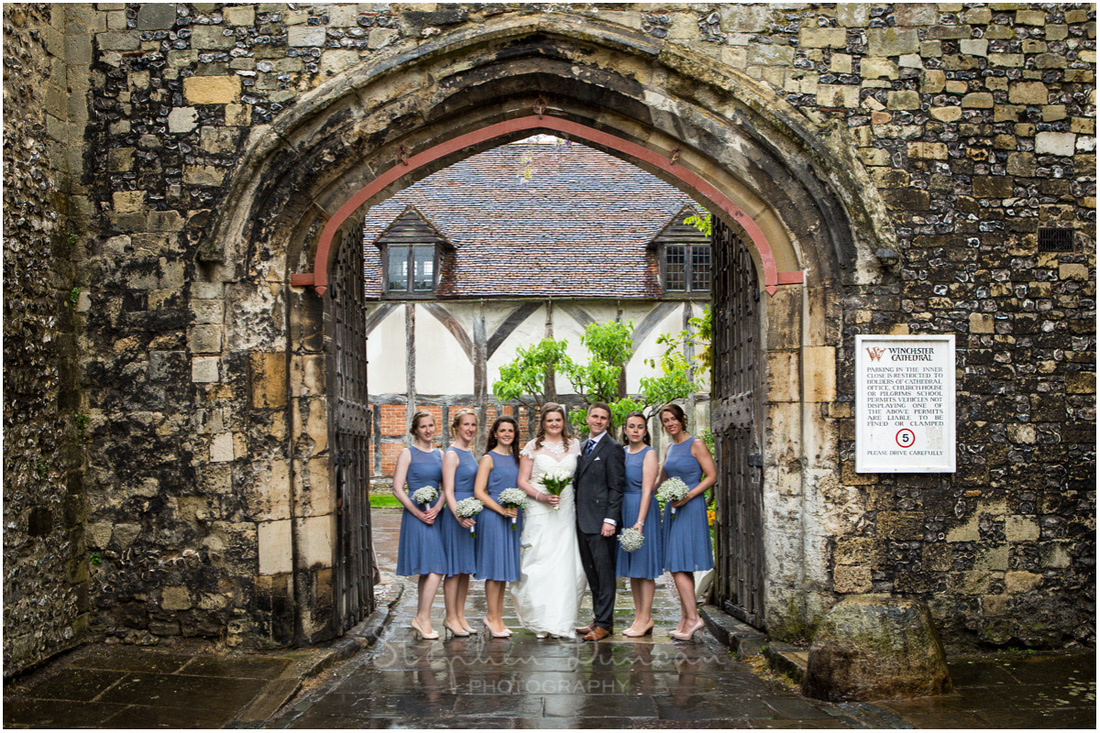 Bride, groom and bridesmaids at the entrance to the Cathedral Close in Winchester
