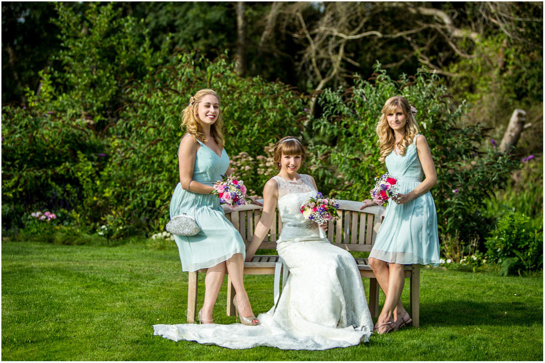 Colour photo of bride and bridesmaids sat on a bench in the gardens of Sopley Mill by the river