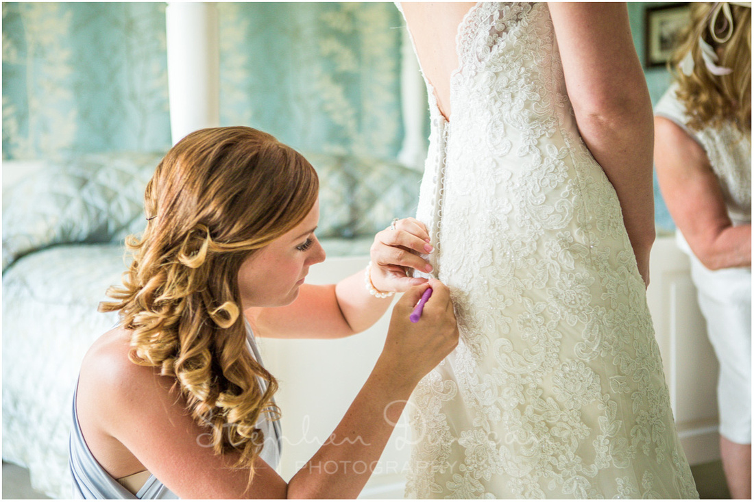 A bridesmaid uses a crochet hook to button up the back of the wedding dress