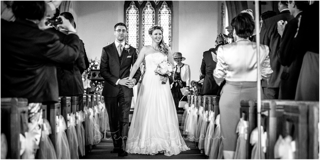 The newly married bride and groom walk back down the aisle together as husband and wife