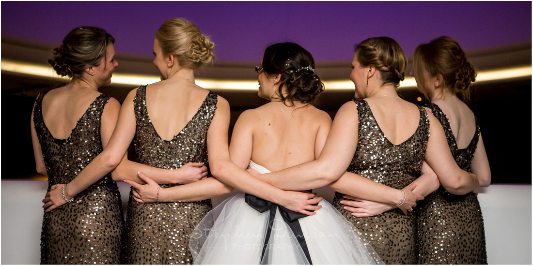 Bride and bridesmaids showing backs of dresses