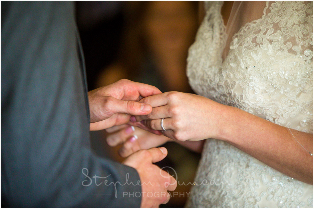 Bride and groom hold hands as they exchange wedding rings