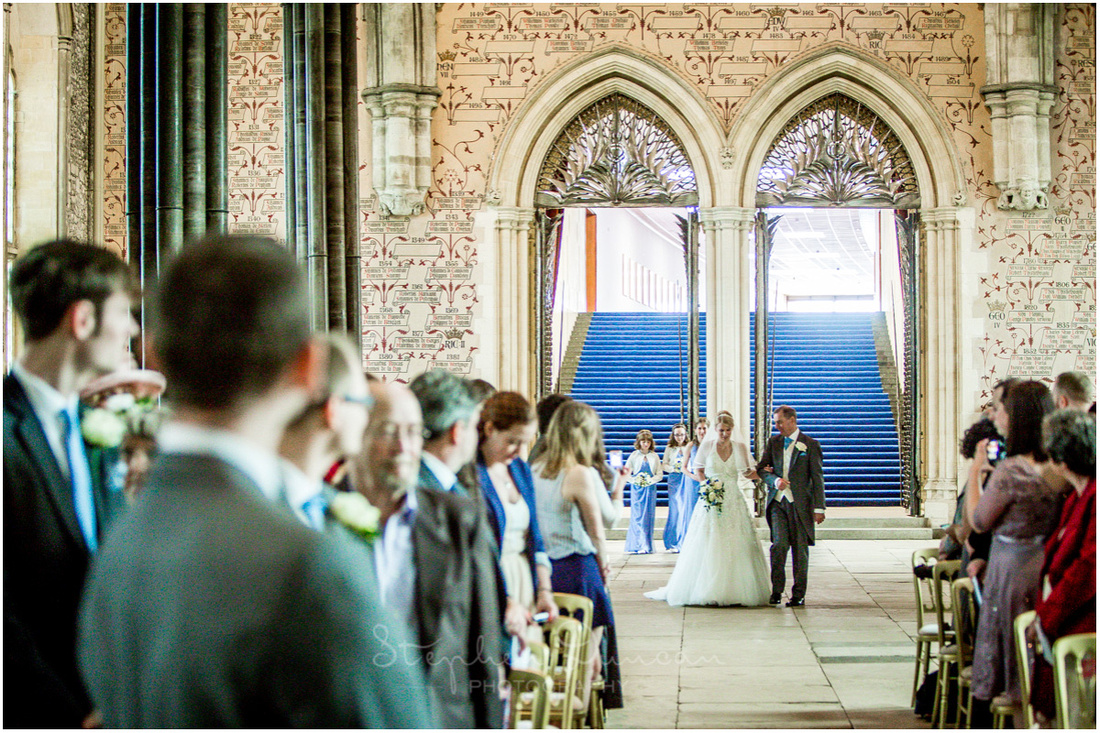 Colour photo of the Great Hall looking towards the rear as the bride walks down the aisle