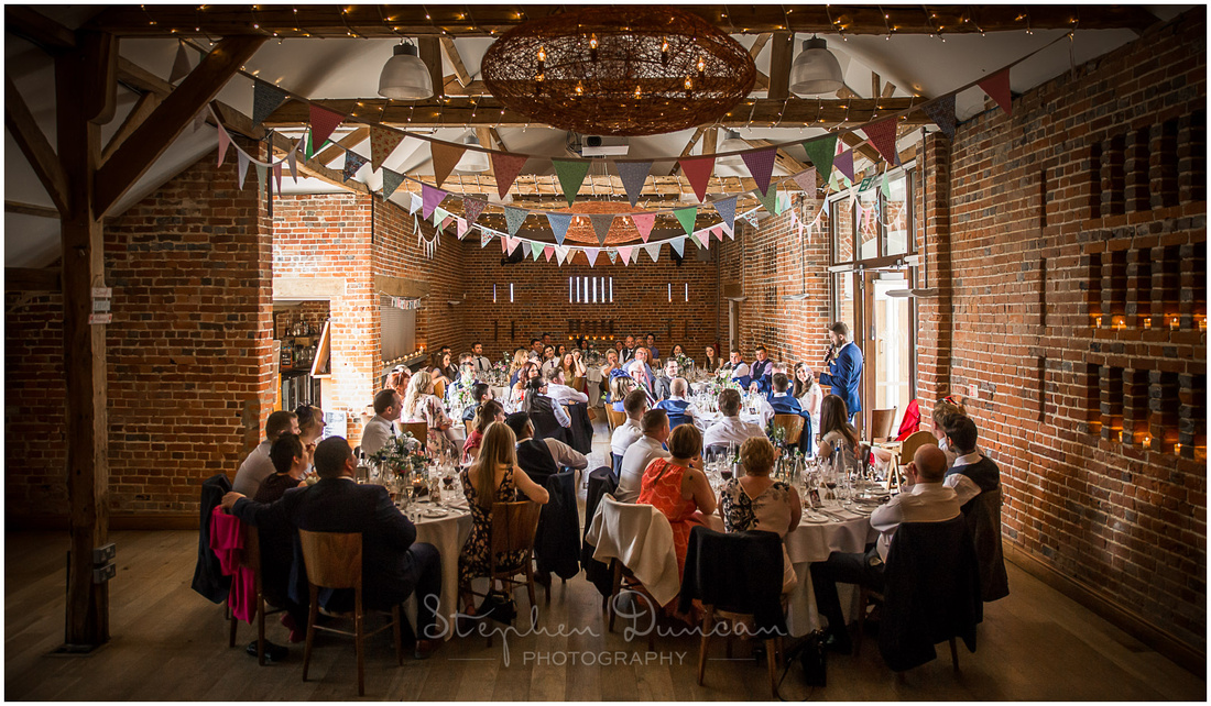 Guests are seated in the old barn watcing on as the groom gives his wedding speech