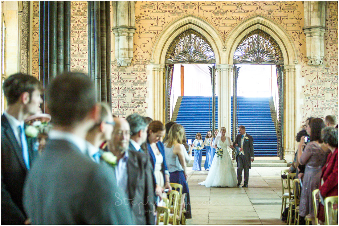 The bride arrives from the back of the hall and walks down the aisle on her father's arm