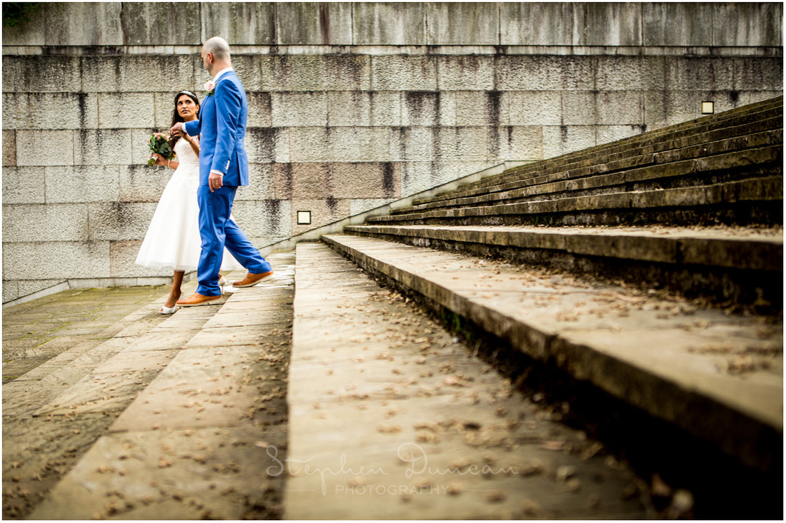 Colour photo of bride and groom descending the steps outside the law courts