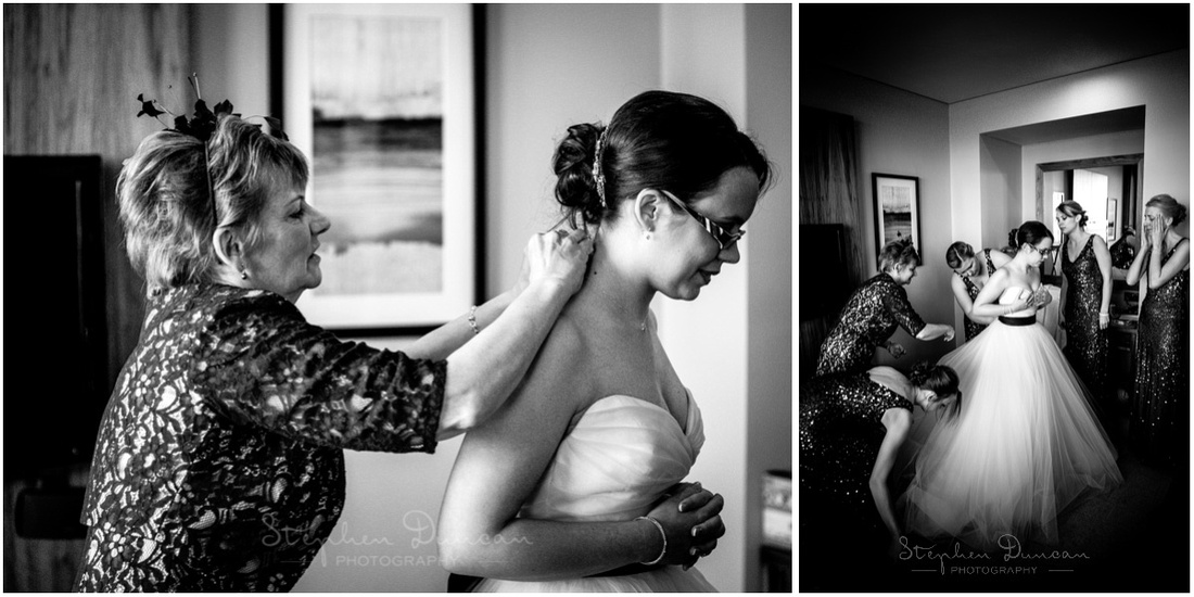 Bride gets into her wedding dress with assistance from her mother