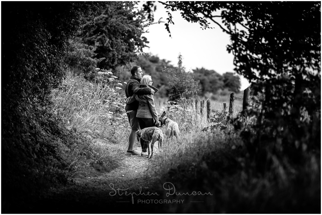 Black and white photo couple looking out across views of South Downs with dogs
