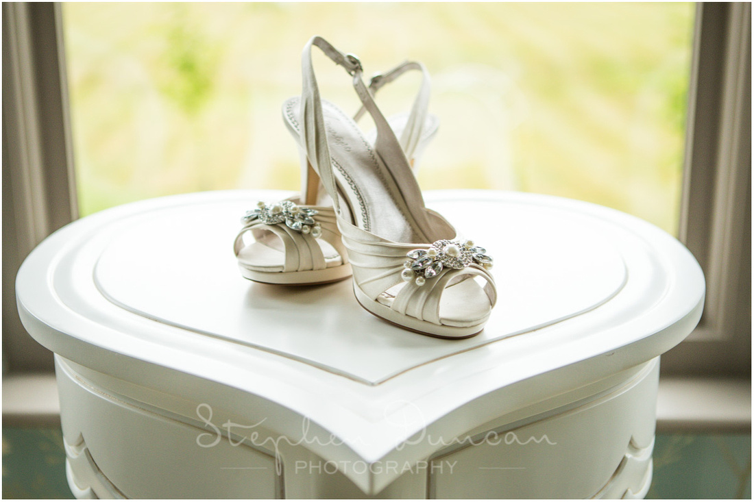 Wedding shoes on heart-shaped table in the bridal suite